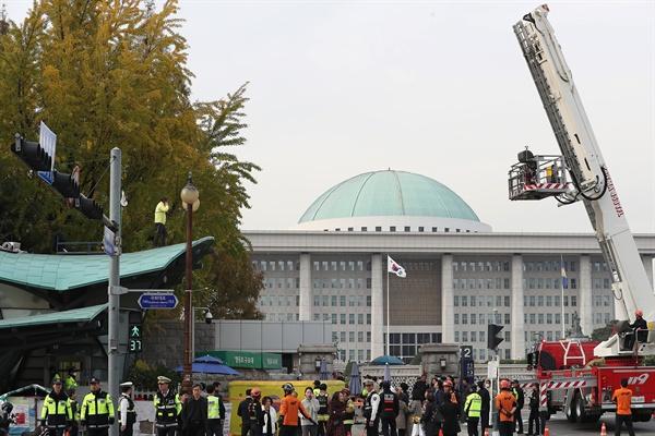 6일 여의도 국회 정문 앞 지하철역 출입구 지붕 위에 '형제복지원 사건 진상규명하라'라고 적힌 점퍼를 입은 한 남성이 시위를 벌이고 있다.
