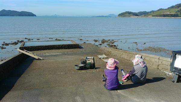 여수 소라면 달천 바닷가, 아낙네가 갯가에 앉아 있다.