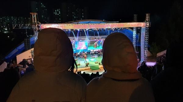 추운 가을 저녁 날씨에 두꺼운 옷을 입은 학생들이 노천극장에서 열리고 있는 동아리 밴드 공연을 감상하고 있다.