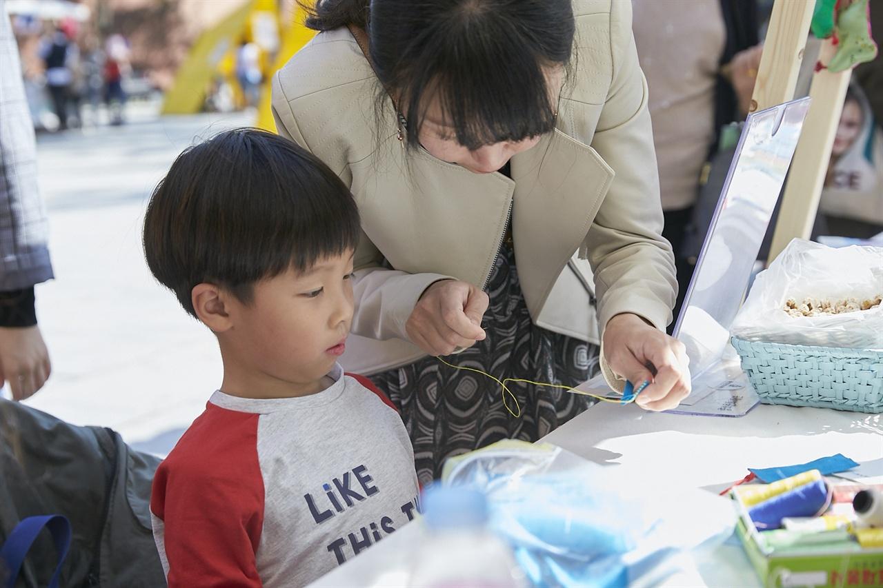 <동임조각보> 부스에서 책갈피 만들기 체험 중인 어린이