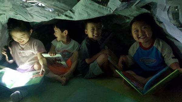 아산 월랑초병설유치원 유아들이 '책 놀이 축제' 기간 중 신문지 텐트 속에서 손전등을 비춰 책을 보는 책 텐트 놀이를 하고 있다.