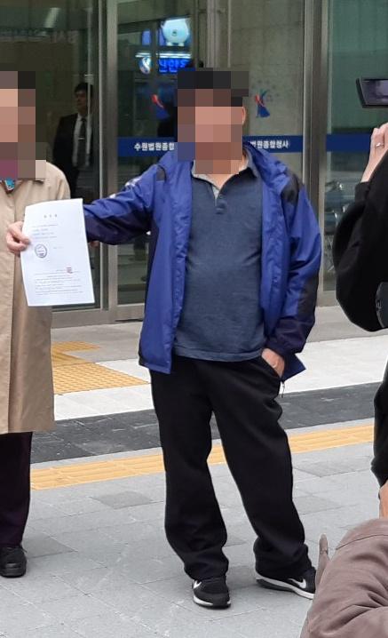 재심 청구인 윤씨가 청구서 제출 뒤 기자들 앞에 서있다.