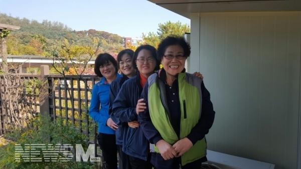 소양관 옥상정원에 새로 준비된 휴게실 입구에서 청소노동자들이 밝게 웃고 있다.