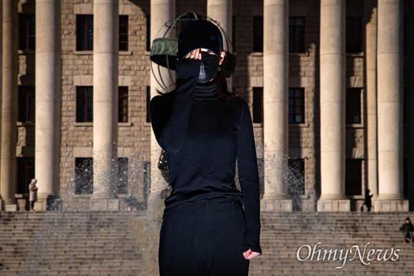 경희대에 재학 중인 홍콩인 유학생이 검정 옷을 입고 홍콩경찰의 고무탄으로 실명이 된 희생자를 상징하는 퍼포먼스를 보이고 있다.