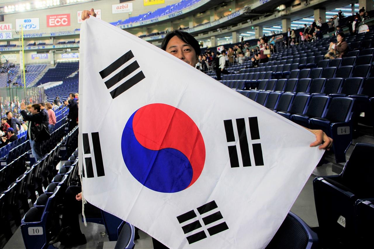 15일 멕시코전에서 열띤 응원을 펼친 일본인 와타나베 씨가 태극기를 들고 서 있다.