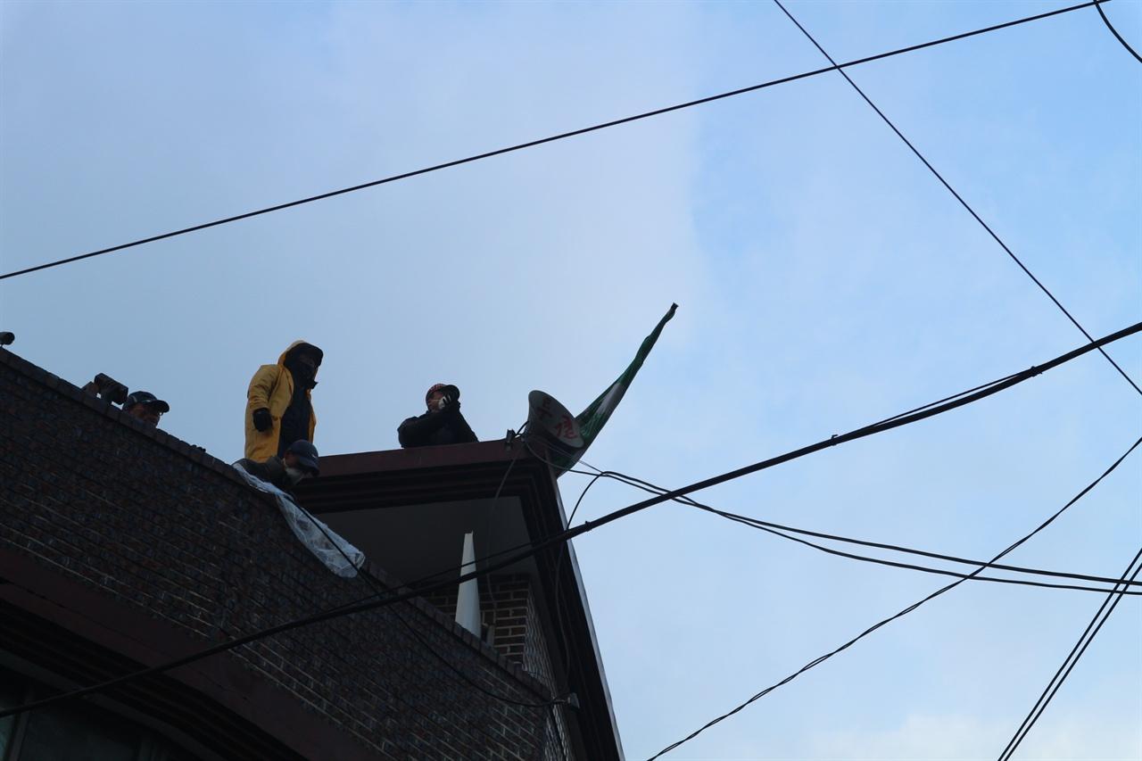 옥상에서 자신들의 억울함을 호소하고 있는 철거민들 강제집행 예정 건물 옥상에서 철거민들이 확성기를 설치하여 자신들의 입장을 설명하고 있다. 이들은 용역에게 '다기오지 말라'라며 절규섞인 말을 했다.