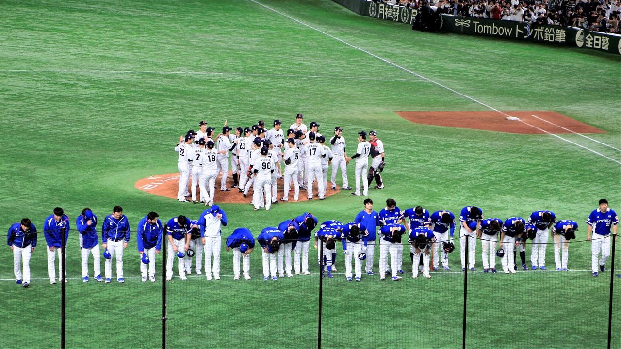 17일 도쿄 돔에서 열린 프리미어 12 결승전에서 패배한 한국 대표팀이 관중들을 향해 인사하고 있다. 뒤의 일본 대표팀이 세레머니를 하는 것과 대비된다.