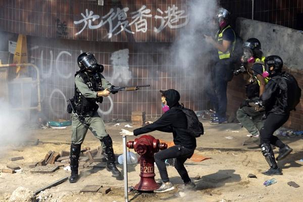 시위 참가자에 무기 겨눈 홍콩 경찰 18일 홍콩이공대학에서 시위진압에 투입된 경찰이 도주하려는 시위대를 향해 진압용 무기를 겨누고 있다.