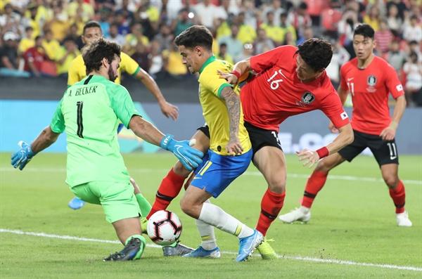 19일(현지시간) 아랍에미리트(UAE) 아부다비 모하메드 빈 자예드 스타디움에서 열린 한국과 브라질 축구 대표팀 평가전에서 한국 황의조가 브라질 쿠티뉴와 골키퍼 알리송을 피해 슈팅을 시도하고 있다.