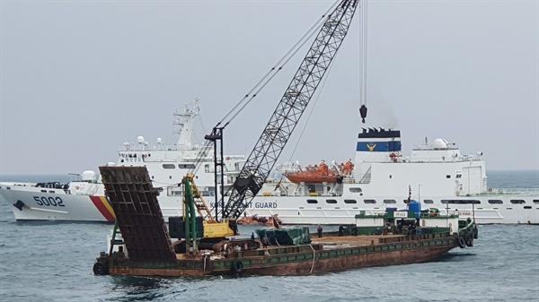 제주해양경찰청은 제주 차귀도 인근 해상에서 화재침몰했던 대성호의 선미 부분을 22일 인양해 바지선에 실어 옮기는 작업을 벌이고 있다.
