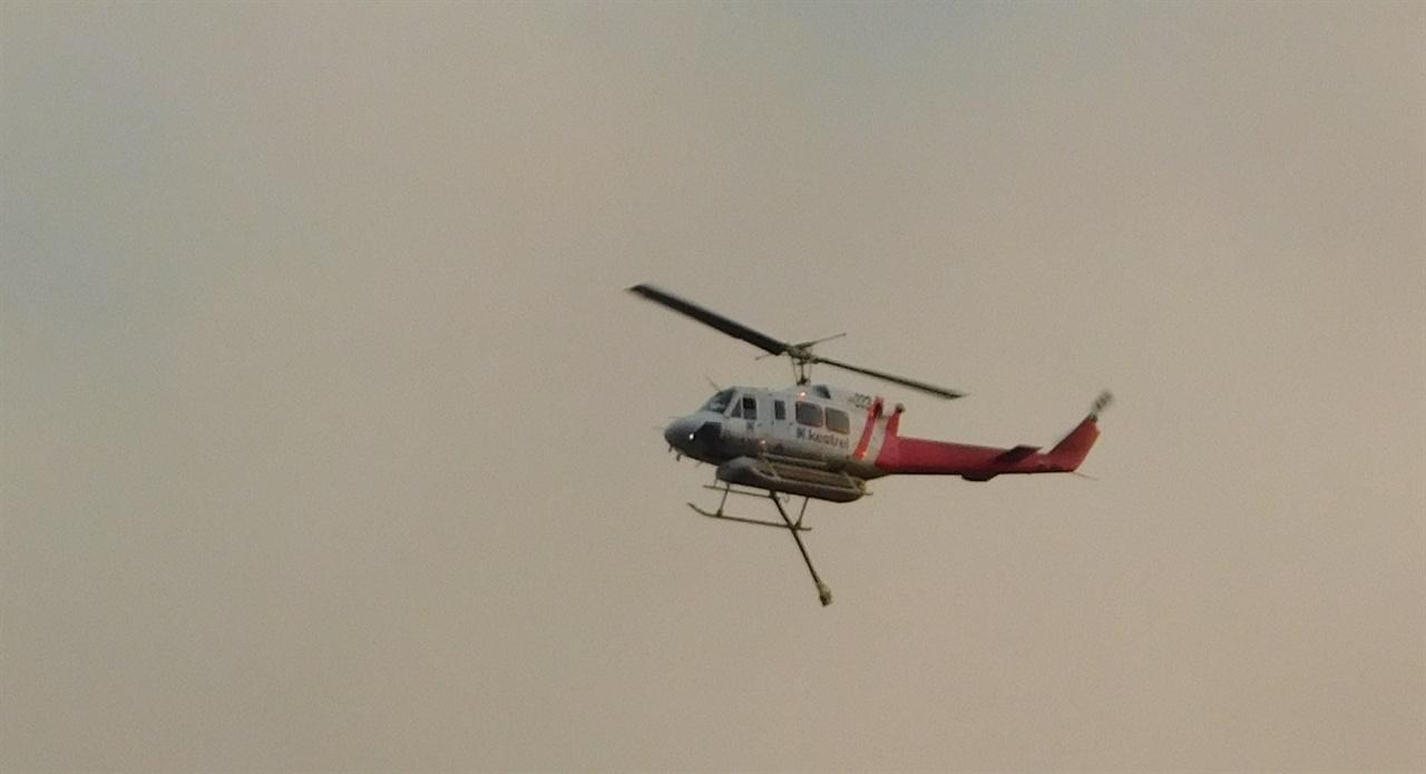 수시로 지붕 위를 오가며 화재 진압에 안간힘을 쏟는 헬리콥터