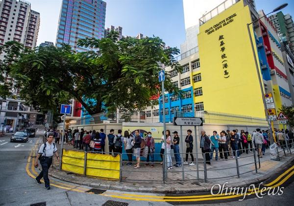 구의원 선거가 치러지는 24일 오전 홍콩 노스포인트 한 학교에 마련된 투표소에서 투표시간이 시작된 직후 부터 시민들이 투표를 하기 위해 길게 줄을 서 있다.