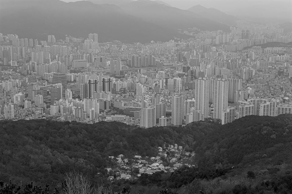 """황령산에서 내려다본 부산의 모습이다. 정남준 사진가는 """"부산에 오시는 분들에게 꼭 추천하는 장소""""라며 """"지금의 사회경제정치를 명징하게 드러내 보이는 부산의 한 현장이다""""라고 하였다. 그리고 """"무엇이 보이나요""""라고 물었다."""