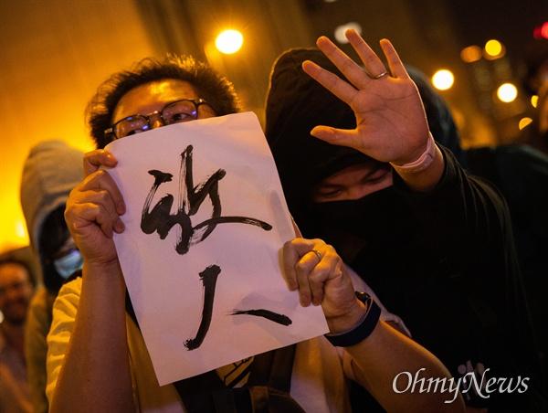 25일 오후 홍콩 이공대학교 앞에서 열린 경찰의 봉쇄로 빠져나오지 못하고 있는 학생 구조 요구 집회에서 억류자를 풀어줄 것을 요구하는 피켓을 들고 있다.