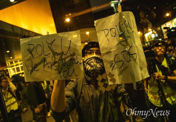 25일 오후 홍콩 이공대학교 앞에서 경찰의 봉쇄로 빠져나오지 못하고 있는 학생들의 구조를 요구하는 집회가 열리 던 중 인근 경찰의 결혼식 피로연장으로 시위대가 몰려가 '폴리유 위드유' 메세지를 남기고 있다.