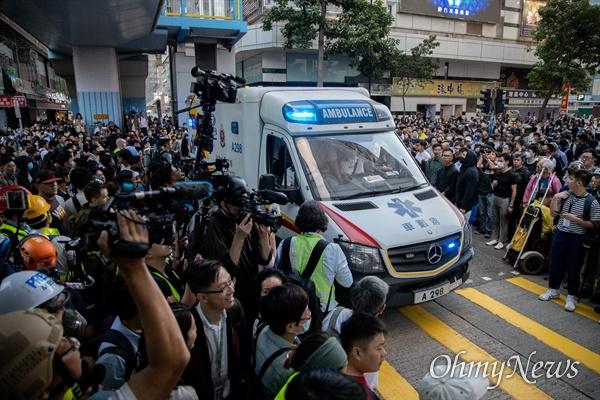 홍콩 구의원 선거가 범야권의 압승 결과로 나온 25일 오후 홍콩 이공대학교 앞에서 경찰의 봉쇄로 빠져나오지 못하고 있는 학생들의 구조를 요구하는 집회가 열리 던 중 엠뷸런스 한대가 학교 내로 들어가고 있다.