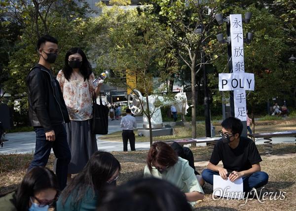 홍콩 구의원 선거가 범야권의 압승 결과로 나온 25일 오후 홍콩 퀀통 한 공원에서 홍콩이공대 내 빠져나오지 못하고 있는 시위대를 위해 지지피켓을 만들고 있다.