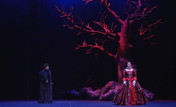 1막 2장 스투아르다(소프라노 이다미)와 로베르토(테너 이재식). 붉고 황량한 나무는 스투아르다의 혈통을 상징한다.