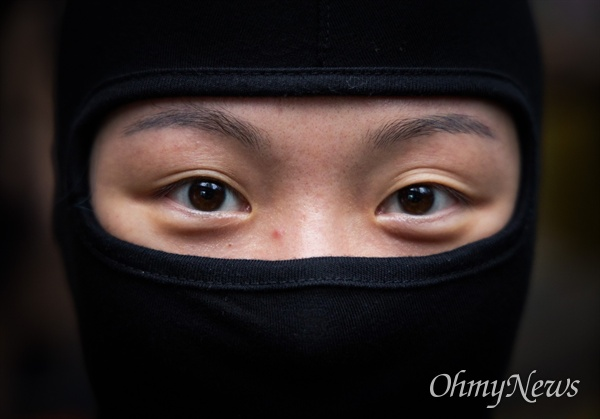 9월 1일 한 20대 청년이 홍콩 5대요구안 수용을 요구하는 시위에 신분을 지키기 위해 복면을 쓰고 참가하고 있다.