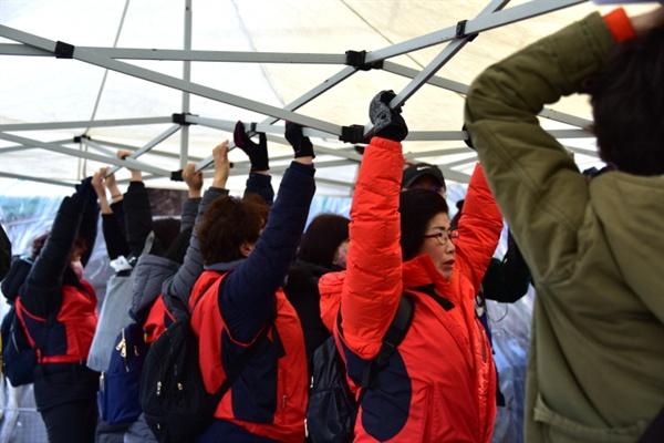 간신히 펼친 천막을 뺏기지 않으려 부둥며 잡고 있는 효림원 노동자들