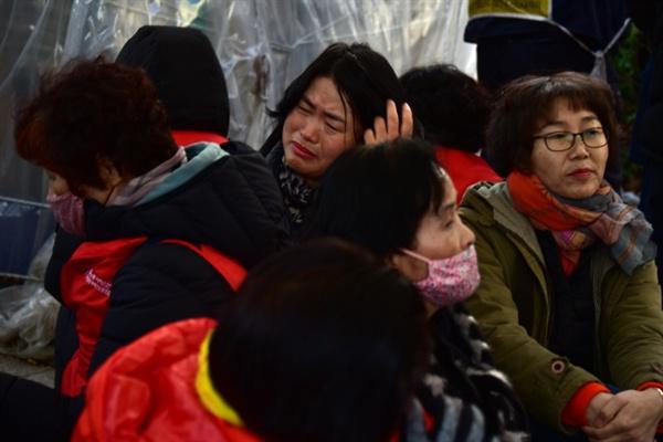 팔레트를 깔고 앉은 효림원 조합원들이 눈물을 흘리고 있다.