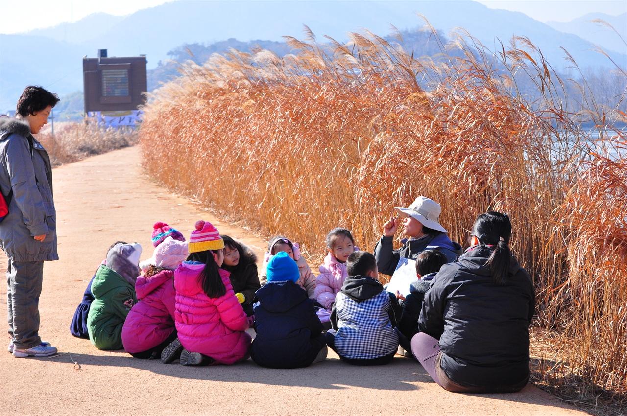 둑 위에 앉아 눈빛을 반짝이며 진지하게 해설사의 설명을 듣고 있는  아이들. 초겨울 주남저수지는 여유롭고 포근하다.