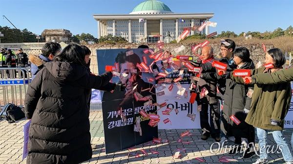 아베규탄시민행동 등 70여 개 시민사회단체가 12월 5일 오후 2시 국회 정문 앞에서 일제강점기 강제동원 피해 문제 해법으로 제시된 '문희상 안' 중단을 촉구하는 기자회견을 열었다. 기자회견을 마친 뒤 아베 일본 총리 얼굴이 담긴 대형 패널에 '사죄 없는 기부금 필요 없다'고 적힌 일본돈 1만 엔짜리 지폐 견본과 '사죄하라!'는 빨간색 경고 딱지를 '머니건'으로 쏘아 붙이는 상징의식을 진행하고 있다.