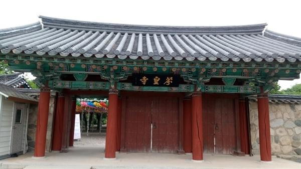 분황사 정문 아담한 기와지붕 아래에 분황사 현판과 붉은 칠을 한 세 개의 문이 달려 있다.