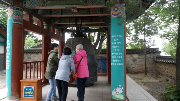 분황사 대종각 방문객들이 천원을 시주하고 종을 치고 있다.