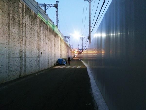 온골마을 높은 기찻길 옹벽과 공사장 펜스 사이 좁은 골목