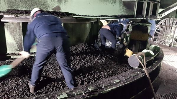 발전소 컨베이어 벨트에서 낙탄을 제거하는 작업을 하고 있는 노동자들