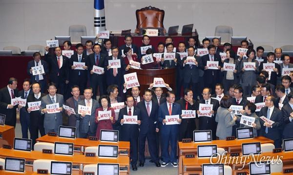 '4+1' 예산 수정안 통과에 '날치기' 피켓 든 한국당 10일 오후 국회 본회의에서 한국당 뺀 '4+1' 예산 수정안이 통과된 후 자유한국당 심재철 원내대표를 비롯한 의원들이 의장석으로 나와 항의하며 피켓을 들어보이고 있다.