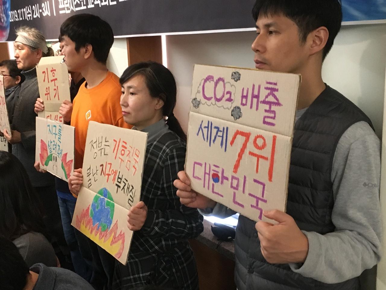 기후위기 비상행동에 참석한 환경단체 회원이 세계 탄소배출량 7위를 기록한 정부를 비판하는 피켓을 들고 있다.