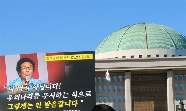 국회 앞에서, 양금덕 할머니의 말 국회 앞 기자회견, 양금덕 할머니의 말이 적힌 피켓이 국회 의사당을 배경으로 보여지고 있다