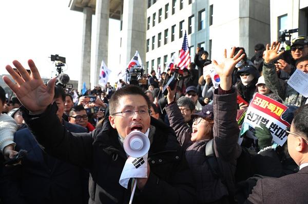 시위대와 함께 한 황교안 자유한국당 황교안 대표가 16일 서울 여의도 국회에서 열린 '공수처법 선거법 날치기 저지 규탄대회' 참가자들과 함께 시위를 벌이고 있다. 이들은 본청 무단 진입을 시도하다 경찰에 막혀 입구에서 집회를 열었다.