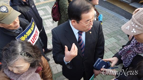 박성중 자유한국당 의원(서울 서초을)이 자유한국당이 주최한 '공수처법, 선거법 날치기 규탄대회' 참석자에게 자신의 개인 전화번호를 알려주고 있는 모습. 이 참가자는 '내일 국회에 들어와야 한다'는 취지로 말하면서 '국회 문을 안 열어줄 경우 전화를 걸 테니 전화번호를 알려달라'고 말했다.