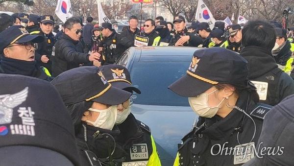 16일 오후 차에 탄 설훈 더불어민주당 의원이 태극기와 성조기를 든 이들에게 가로막힌 모습.