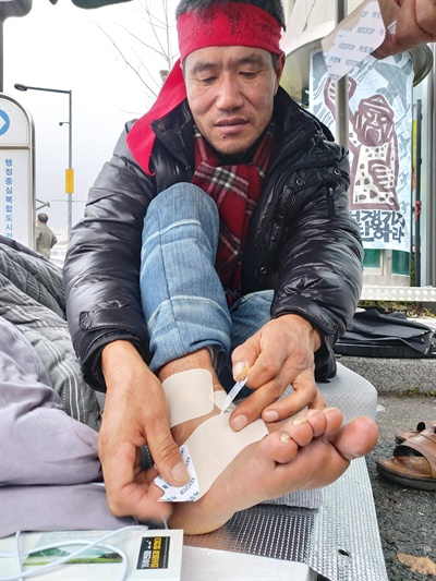 환경부 세종청사 앞에서 7일째 단식농성중인 김경배 씨가 차 사고로 다친 발목에 파스를 붙이고 있다.