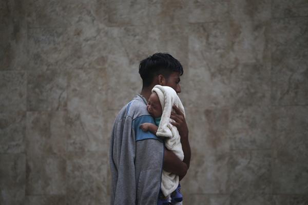 2018년 10월 21일 멕시코 타파출라에 도착한 이주자 카라반 참가자 남성이 자신의 아들을 안고 어디론가로 가고 있다. 그는 트럭 운전사가 무료로 태워줬다고 말했다.