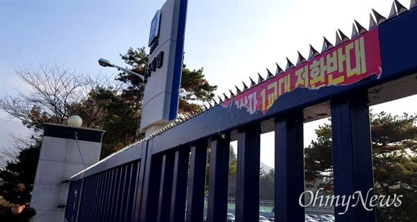 한국지엠 창원공장 정문에 비정규직들이 '함께 살자'는 딱지를 붙여 놓은 가운데, 회사는 정문 위에 뾰족한 철심을 박아놓았다.