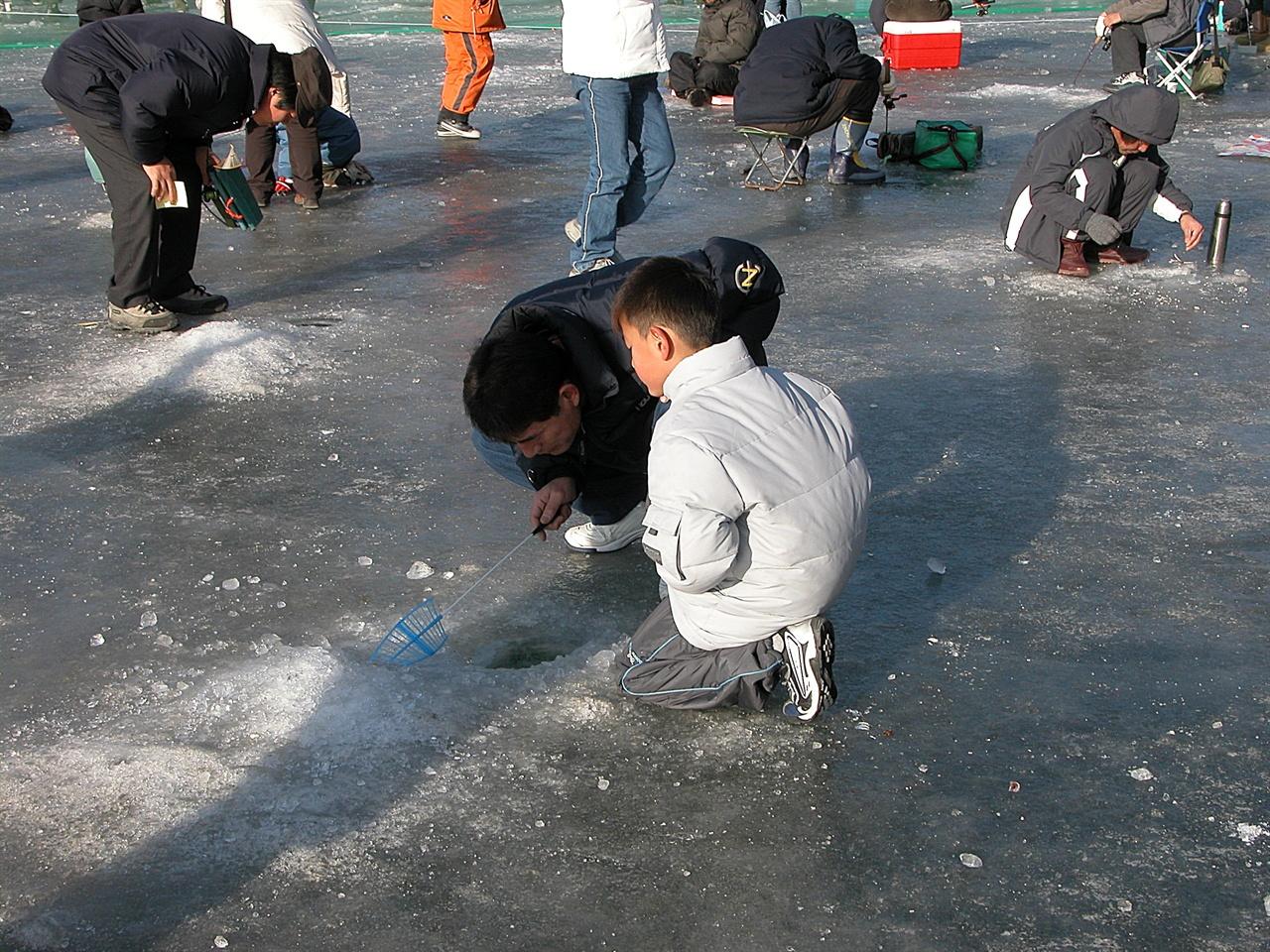 화천 산천어축제 축제장 얼음 낚시터에는 겨울 추위에도 아랑곳없이 산천어를 잡고자 하는 사람들이 무수히 많다.