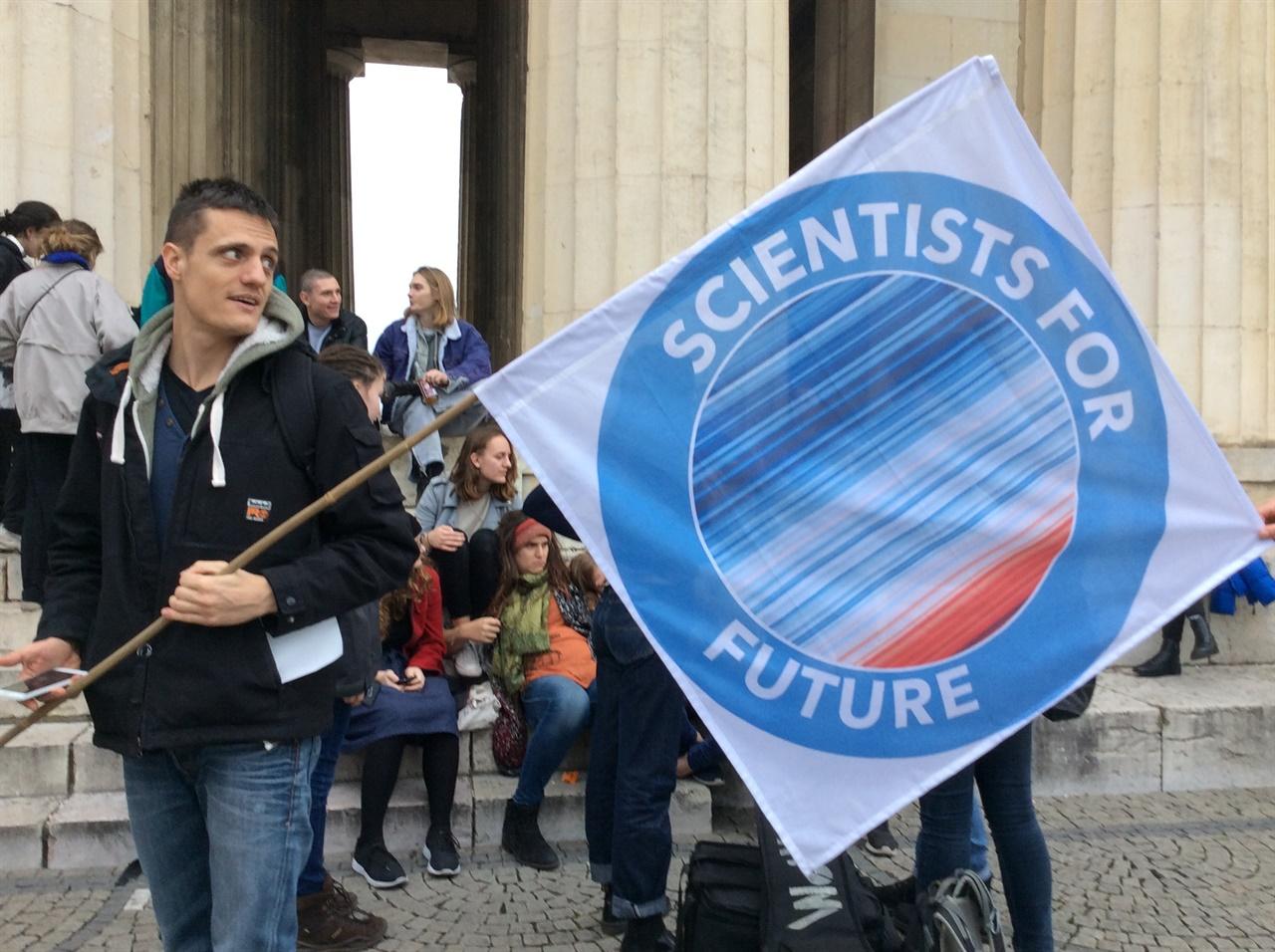미래를 위한 과학자들 '미래를 위한 과학자들(Scientists For Future)' 뮌헨 회원이 깃발을 들며 기후위기 집회에 참가하고 있다.