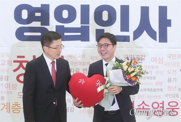 황교안 자유한국당 대표가 8일 오전 서울 여의도 국회 의원회관에서 열린 2020년 영입인사 환영식에서 탈북자 출신 북한인권활동가 지성호 NAHU(나우) 대표를 소개하며 꽃다발과 '자유'라고 적힌 쿠션을 선물하고 있다.