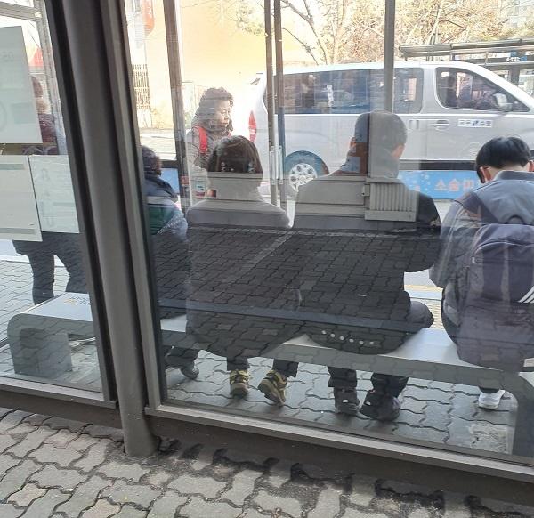 온열의자에 앉아 버스를 기다리고 있는 주민들.