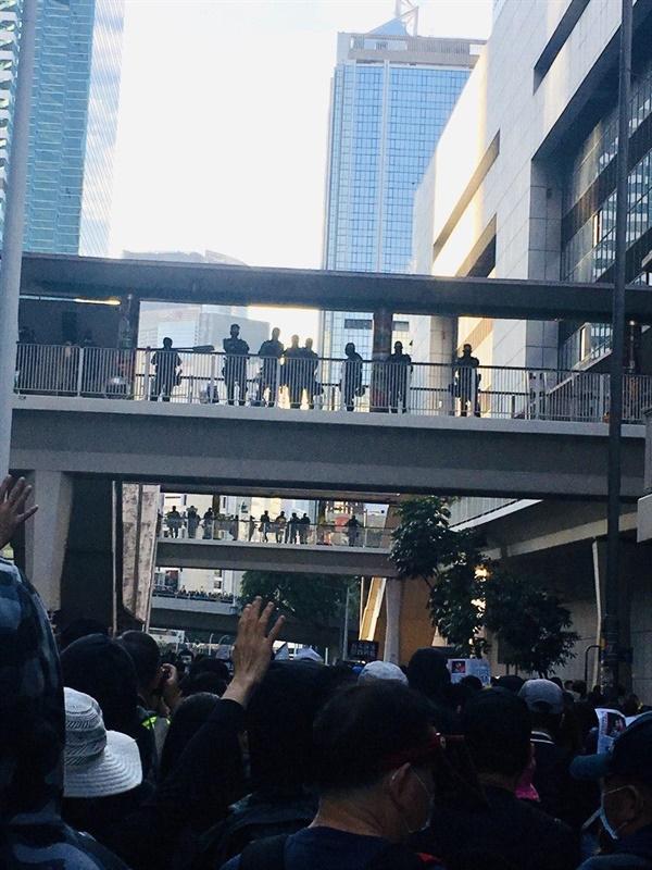 """경찰본부의 육교 위에서 경찰들이 행진 참가자들을 내려다보고 있고 시민들을 그 모습을 보고 """"경찰 해체""""를 외쳤다"""