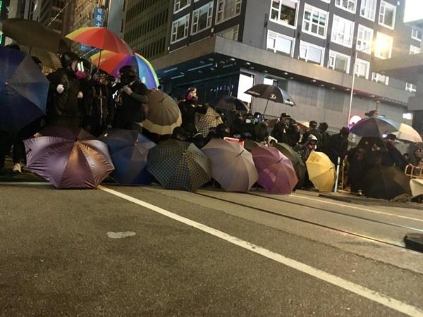 센트럴의 무장한 경찰에 맞서 검은 옷의 프론트 라인이 바리케이드로 저지선을 만들고 있다.