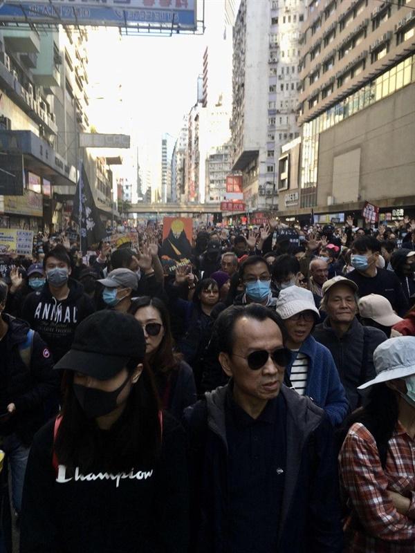 도로를 채운 행진 참가자들이 손을 펼치며 5대 요구를 외치고 있다