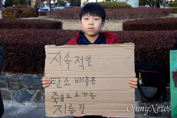경남 창원과 김해지역의 초등학교와 중학교에 다니는 어린이들이 13일 오후 경남도청 정문 앞에서 '기후위기'를 고발하는 행동에 나섰고, 박지호 학생(가포초교 5년)이 집에서 종이상자를 활용해 만든 손팻말을 들고 나왔다.