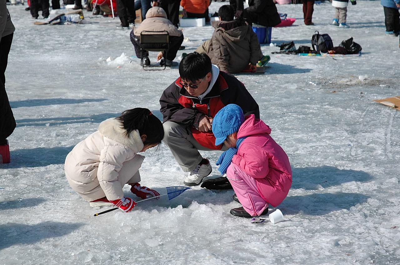 한마리라도 잡아야 할 텐데... 빙어낚시에 열중하는 아빠와 아이들의 표정이 무척 진지하다(사진은 2018년 인제 빙어축제).
