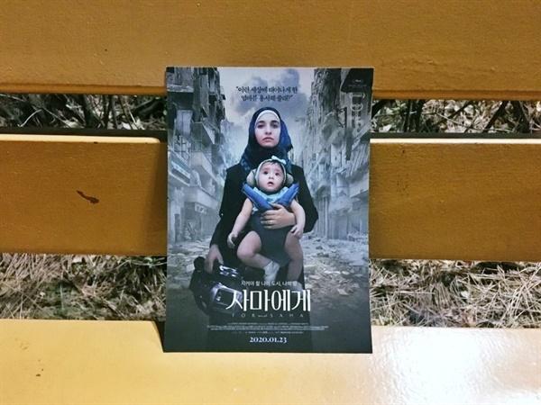 사마를 안고 있는 와드 알-카팁의 모습이 담긴 <사마에게> 포스터